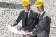 Retrato de los hombres de negocios jovenes confiados en cascos que examinan el modelo al aire libre Foto de archivo libre de regalías