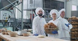 Retrato de los hombres de la panadería dos de la industria y de los panaderos de la mujer que mira derecho a la cámara y a la muj almacen de video