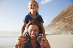 Retrato de los hombros de Carrying Son On del padre el vacaciones de la playa imagen de archivo