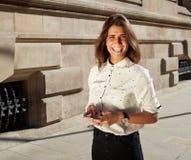 Retrato de los jóvenes que sueñan el teléfono móvil de la tenencia femenina mientras que da un paseo en la ciudad, mujer atractiv Foto de archivo libre de regalías
