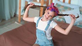 Retrato de los juegos de la muchacha de las sonrisas con las trenzas largas, muecas en la cámara, cámara lenta metrajes