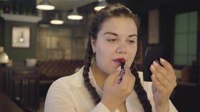 Retrato de los labios de pintura de la mujer regordeta confiada atractiva con la barra de labios roja brillante en el restaurante almacen de metraje de vídeo
