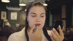 Retrato de los labios de pintura de la mujer regordeta confiada atractiva con la barra de labios roja brillante en el restaurante almacen de video