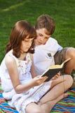 Retrato de los libros de lectura lindos de los niños en el ambiente natural Foto de archivo