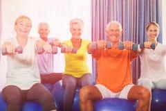 Retrato de los mayores que usan la bola y pesos del ejercicio Foto de archivo