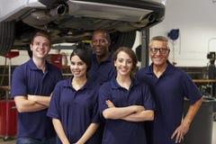 Retrato de los mecánicos de automóviles que trabajan en garaje foto de archivo