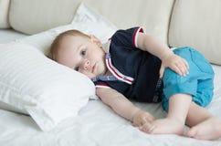 Retrato de los 10 meses lindos del bebé en camiseta y pantalones cortos que mienten en la almohada grande en cama Fotos de archivo libres de regalías
