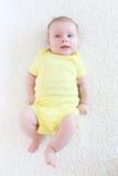 Retrato de los 2 meses preciosos de bebé en mono amarillo Fotos de archivo libres de regalías