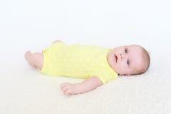 Retrato de los 2 meses preciosos de bebé en mono amarillo Fotografía de archivo