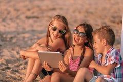 Retrato de los ni?os positivos que r?en el v?deo divertido de observaci?n en la tableta digital en la playa arenosa fotografía de archivo