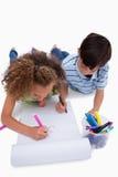 Retrato de los niños que dibujan mientras que miente en el piso foto de archivo libre de regalías