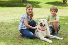 Retrato de los niños que juegan con el perro casero en el parque Imagen de archivo libre de regalías