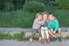 Retrato de los niños que se sientan en el encintado Foto de archivo