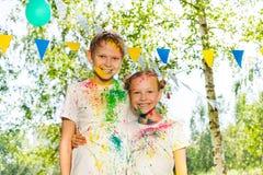 Retrato de los niños felices manchados con el polvo coloreado Foto de archivo