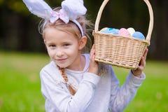 Retrato de los oídos del conejito de la niña que llevan con los huevos de Pascua llenos de la cesta el día de primavera al aire l Imagen de archivo