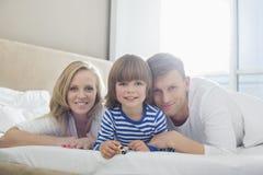 Retrato de los padres felices que mienten con el hijo en cama Foto de archivo libre de regalías