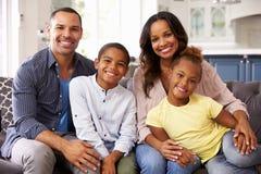 Retrato de los padres y de los niños jovenes que se relajan en casa Imágenes de archivo libres de regalías
