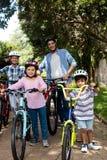 Retrato de los padres y de los niños que se colocan con la bicicleta en parque Foto de archivo