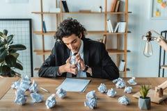 retrato de los papeles de arrugamiento enojados del hombre de negocios en el lugar de trabajo Foto de archivo