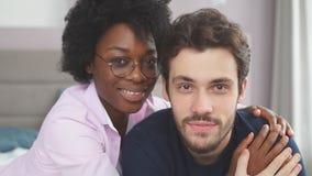 Retrato de los pares de amor de la raza mixta joven que tienen épocas románticas en dormitorio almacen de video