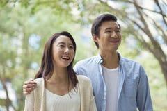 Retrato de los pares asiáticos jovenes que se colocan y que sonríen al aire libre Imagen de archivo