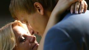 Retrato de los pares atractivos jovenes de los recienes casados que abrazan y que se besan blando en el iluminado por el sol almacen de video