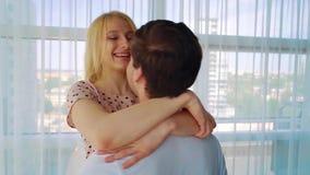 Retrato de los pares cariñosos jovenes que hacen girar alrededor junto en casa por la mañana metrajes
