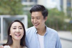 Retrato de los pares chinos jovenes que se colocan y que sonríen al aire libre Imagen de archivo libre de regalías
