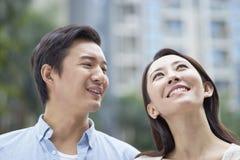 Retrato de los pares chinos jovenes que se colocan y que sonríen al aire libre en jardín Foto de archivo libre de regalías