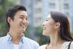 Retrato de los pares chinos jovenes que se colocan y que sonríen al aire libre en jardín Foto de archivo