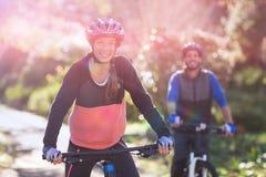 Retrato de los pares del motorista que completan un ciclo en campo Imagen de archivo libre de regalías