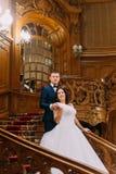 Retrato de los pares elegantes del recién casado que presentan en las escaleras en interior rico en la mansión clásica vieja Foto de archivo