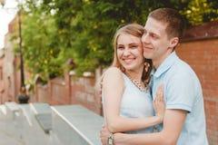 Retrato de los pares felices que abrazan el fondo de risa de la pared de ladrillos Foto de archivo