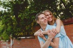 Retrato de los pares felices que abrazan el fondo de risa de la pared de ladrillos Imagen de archivo libre de regalías