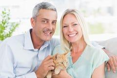 Retrato de los pares felices que juegan con el gato Fotos de archivo libres de regalías