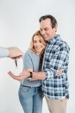 Retrato de los pares felices que reciben llaves de nueva casa foto de archivo