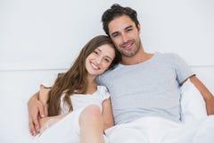 Retrato de los pares felices que se sientan en cama imagen de archivo libre de regalías