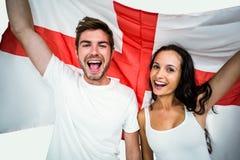 Retrato de los pares felices que sostienen la bandera inglesa Imagenes de archivo