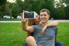 Retrato de los pares felices que toman un selfie en el parque Foto de archivo
