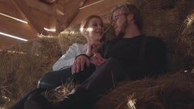 Retrato de los pares jovenes bonitos que mienten en el heno en el granero frío del invierno Granjero joven que descansa después d metrajes