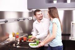 Retrato de los pares jovenes felices que cocinan junto en la cocina Fotografía de archivo libre de regalías