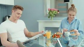 Retrato de los pares jovenes felices que hablan y que ríen durante el desayuno en casa metrajes