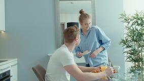 Retrato de los pares jovenes felices que hablan y que ríen durante el desayuno en casa almacen de metraje de vídeo
