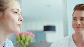 Retrato de los pares jovenes felices que hablan y que ríen durante el desayuno en casa almacen de video