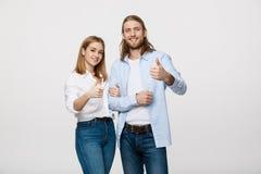 Retrato de los pares jovenes felices que muestran el pulgar para arriba aislado en el fondo blanco Fotografía de archivo