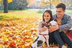 Retrato de los pares jovenes felices que se sientan al aire libre en parque del otoño Fotos de archivo libres de regalías
