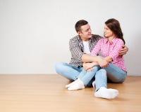 Retrato de los pares jovenes felices que se sientan en piso Foto de archivo