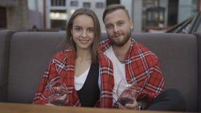 Retrato de los pares jovenes felices que sonríen en la cámara Vidrios con el vino honeymoon almacen de metraje de vídeo