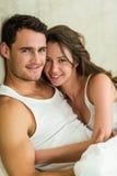 Retrato de los pares jovenes que abrazan en cama Fotografía de archivo