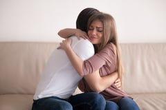 Retrato de los pares jovenes que abrazan la sentada apretada en el sofá dentro Foto de archivo libre de regalías